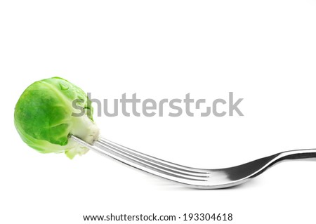 Fresh brussel sprout on fork against white background.
