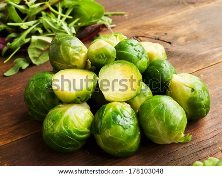 Fresh brussel sprouts on the wooden background. Shallow dof. - stock photo