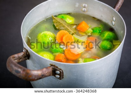 Fresh Brussels sprouts soup in a pot on black wooden table