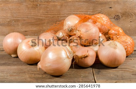 Fresh bulbs of onions on wooden background