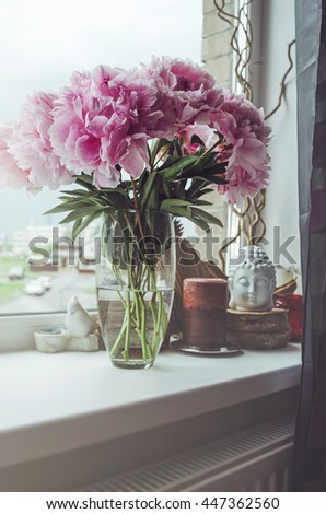 Fresh bunch of pink peonies roses flowers, green leaf in glass vase on the window sill, white background. Summer time concept. Still life, rustic style. Fresh floral, home decor. Text, copy space - stock photo