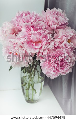 Fresh bunch of pink peonies roses flowers, green leaf in glass vase on the window sill, white background. Summer time concept. Still life, rustic style. Fresh floral, home decor. Text, copyspace - stock photo