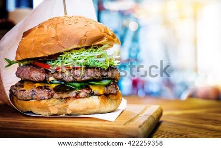 Fresh burger closeup on wooden table. - stock photo