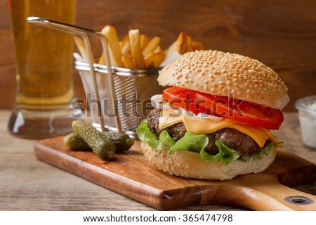 Fresh burger closeup with cheese, sauce and potatoes, selective focus - stock photo