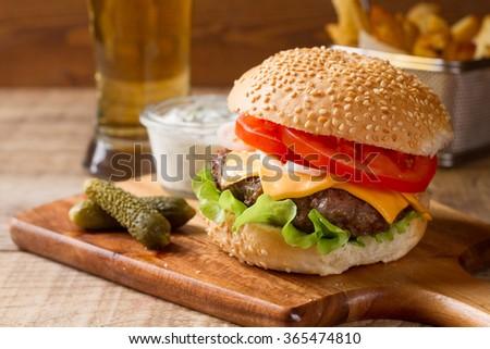 Fresh burger closeup with cheese, sauce and potatoes, selective focus - stock photo