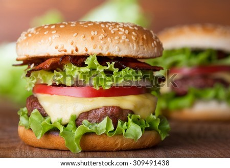 fresh burger with cheese and bacon on wooden table - stock photo