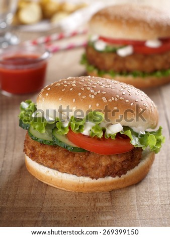 Fresh burger with vegetables on  wooden background, selective focus - stock photo