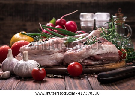 Fresh butcher cut meat assortment garnished with fresh rosemary on wooden table
