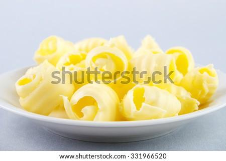 Fresh butter curls on dish closeup - stock photo
