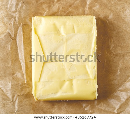 Fresh butter on pergament paper, top view - stock photo
