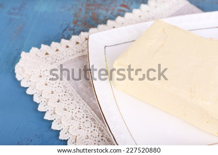 Fresh butter on plate, on wooden background