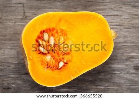 Fresh butternut squash slice on wooden table - stock photo