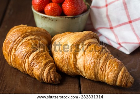 Fresh buttery croissants on brown wooden table, kitchen cloth and bowl with strawberries, close up - stock photo