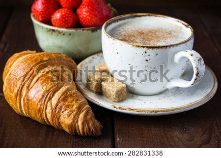 Fresh buttery croissants on wooden table, hot cup of coffee and bowl with strawberries, close up - stock photo