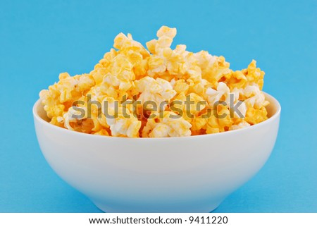 Fresh buttery popcorn with a colorful blue background. - stock photo
