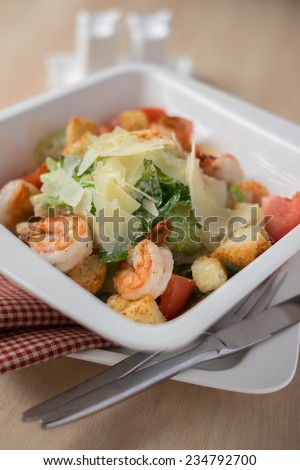 Fresh Caesar salad with shrimps, salad leaves, tomatoes, freshly shredded parmesan cheese in a deep serving plate on a wooden table - stock photo