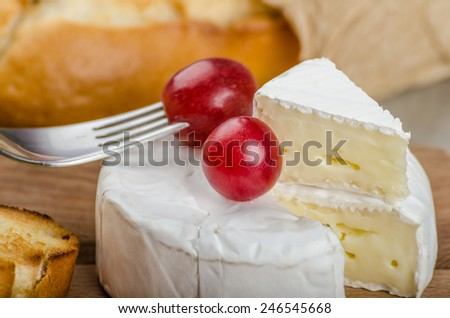 Fresh camembert from organic farms with red grapes and toasted baguette