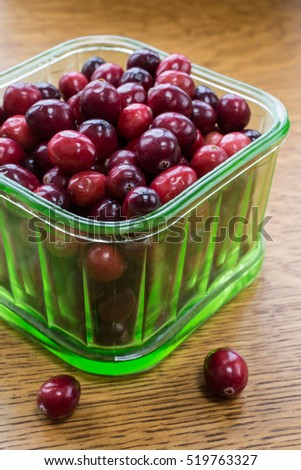 Fresh Cape Cod ripe red cranberries in a depression green glass bowl.