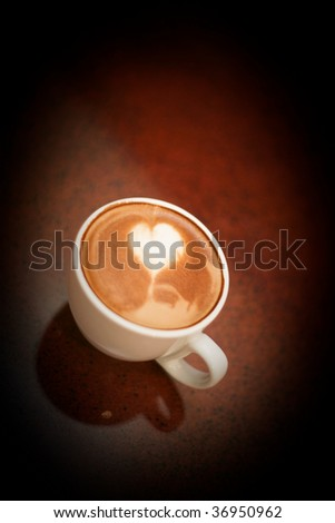 fresh cappuccino with a heart shaped in the top of the frothy steamed milk - stock photo