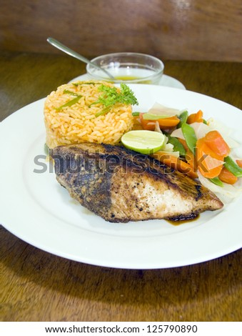 fresh Caribbean style yellowfin tuna steak with vegetables rice as photographed in Union Island St. Vincent and the Grenadines - stock photo