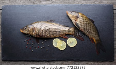 Fresh carps with peppers and lemon on black cutting board
