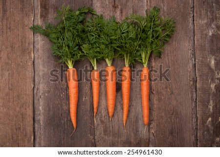 fresh carrot bunch on grungy wooden background - stock photo