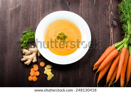 Fresh carrot ginger soup with ingredients on background - stock photo