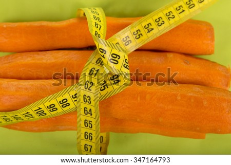 Fresh carrots and centimeter on a green background
