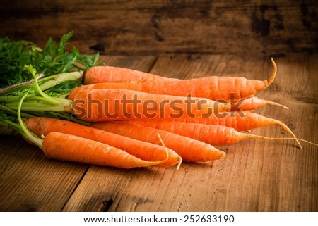 fresh carrots bunch on rustic wooden background - stock photo