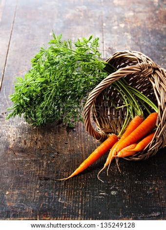 Fresh carrots in basket on wooden background - stock photo