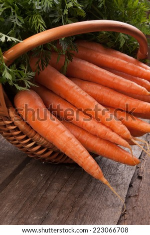 fresh carrots in wicker basket bunch on grungy wooden background - stock photo