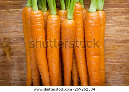 Fresh carrots on a wooden background. - stock photo