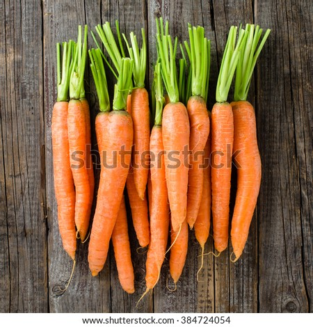 Fresh carrots on wooden table - stock photo