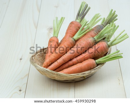 Fresh Carrots organic vegetables in basket on wooden background - stock photo