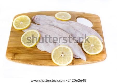 Fresh catfish fillets on a cutting board with lemon and isolated on  white. - stock photo