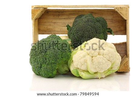 Fresh cauliflower and broccoli in a wooden crate on a white background - stock photo