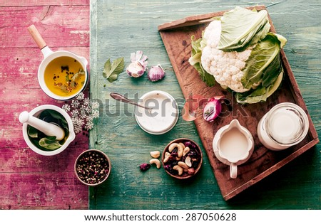 Fresh cauliflower with savory ingredients for a gourmet vegetarian dish standing ready to prepare the meal on a colorful shabby chic wooden background - stock photo