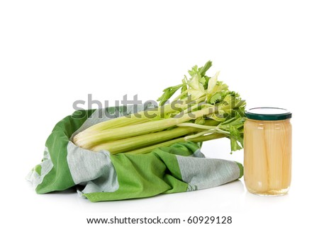 Fresh celery  in a basket versus canned celery in a jar, on reflective surface. Studio shot. White background. Copy space. - stock photo