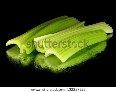 fresh celery on a black background with water drops