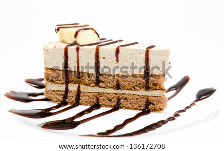 fresh cheese cake with chocolate syrup and piece of banana - stock photo
