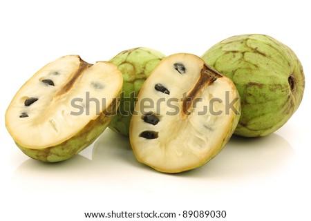 fresh cherimoya fruits (Annona cherimola) and a cut one on a white background - stock photo