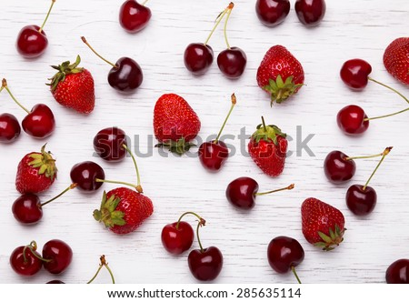 Fresh cherries and strawberries on the white wooden table, top view - stock photo