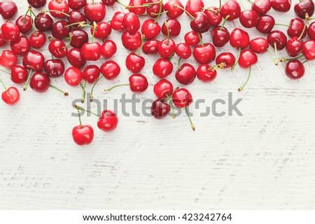 Fresh cherries. Freshly picked sweet cherries on wooden table - stock photo