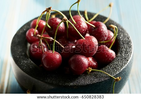Fresh cherries in a jar on a blue wooden table