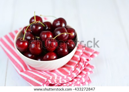 Fresh Cherries in a white bowl on white table