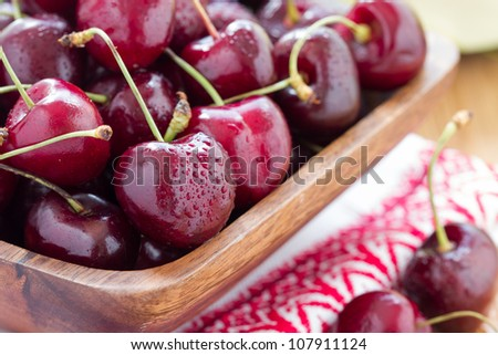 fresh cherries in basket on wood table - stock photo