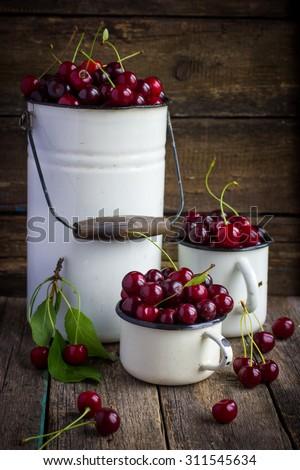 fresh cherries in enamel kitchenware on wooden background, summer harvest. - stock photo