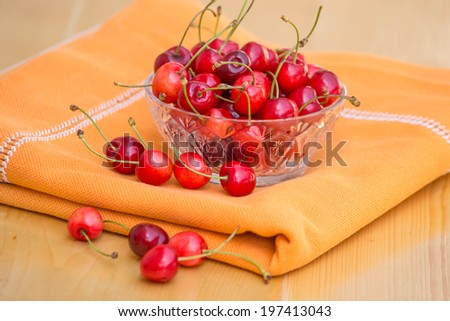 Fresh cherries in transparent bowl on wood table with texture
