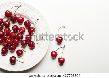 Fresh cherries on a plate and white background.