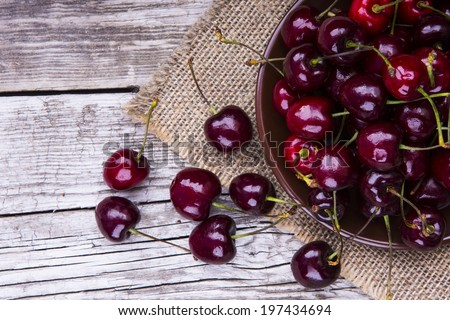 fresh cherries on wooden table - stock photo